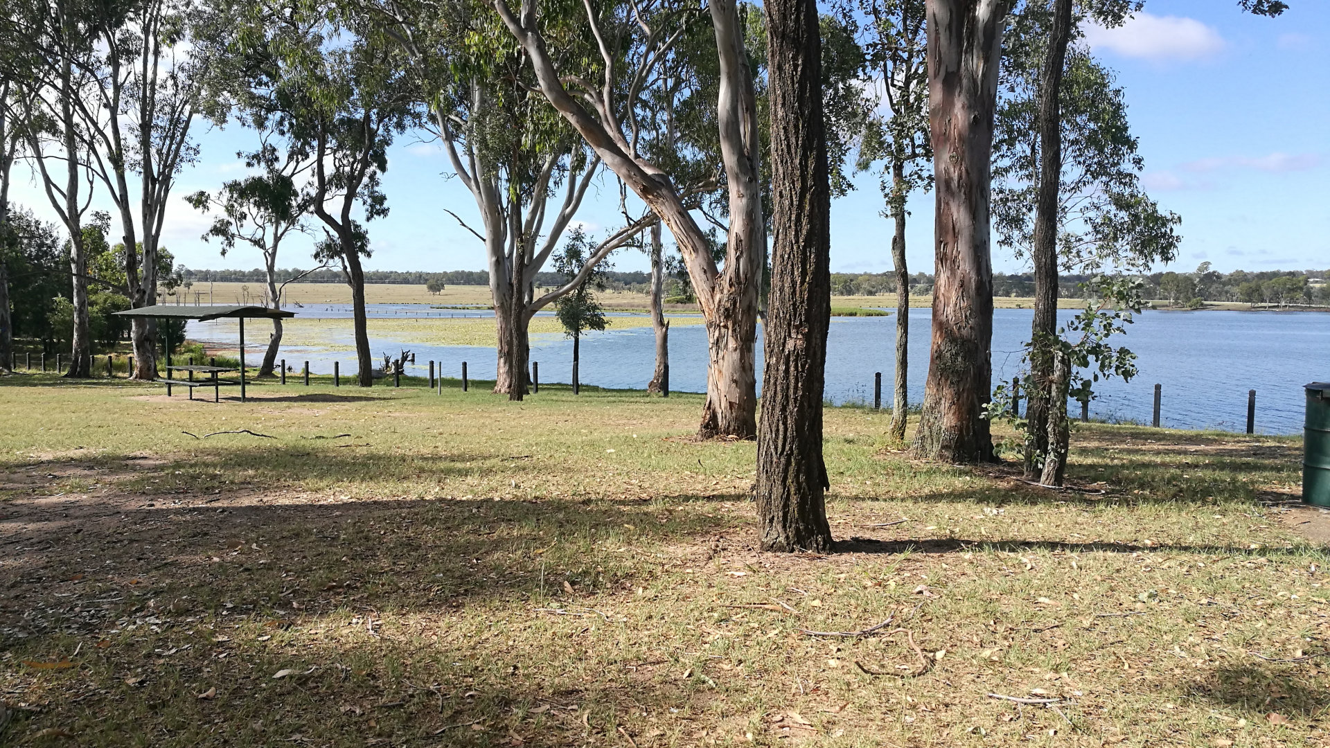 Grass area of Gordonbrook Dam with picnic table and dam water in the background. Gordonbrook Dam is the water supply to Kingaroy, with a day use area, walking trails, and bird hide