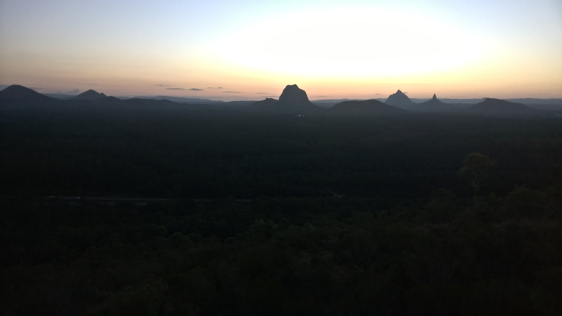 View at dusk looking west from Wild Horse Mountain Lookout with Glass House Mountains peaks on the horizon. The lookout has 360 degree views including towards Brisbane, Redcliffe, Moreton Island, Bribie Island, and more