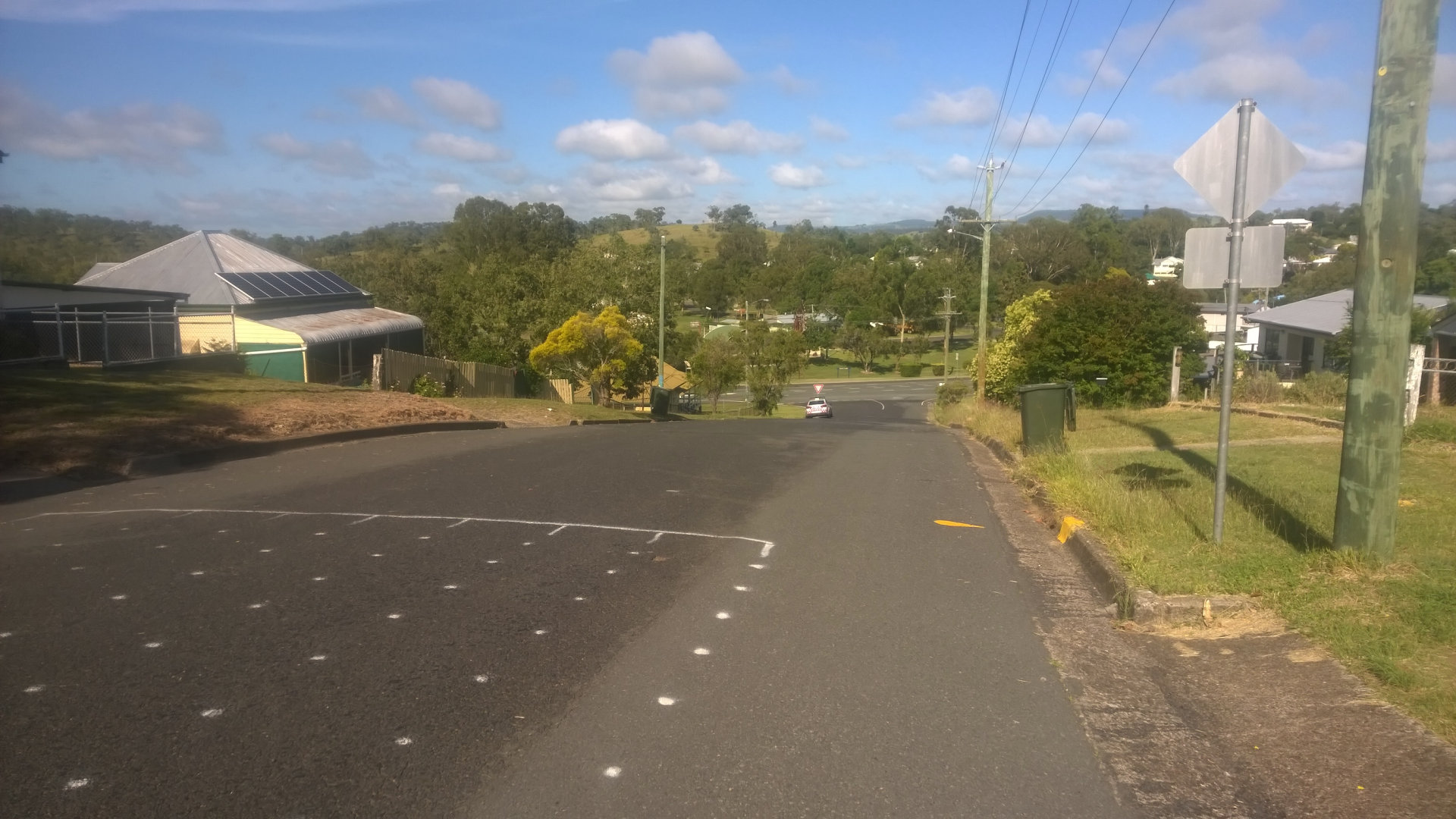 Looking down the Policeman's Hill with lane markings for the Pumpkin Festival on the road. The hill used during the Goomeri Pumpkin Festival, an annual event held on the last Sunday in May