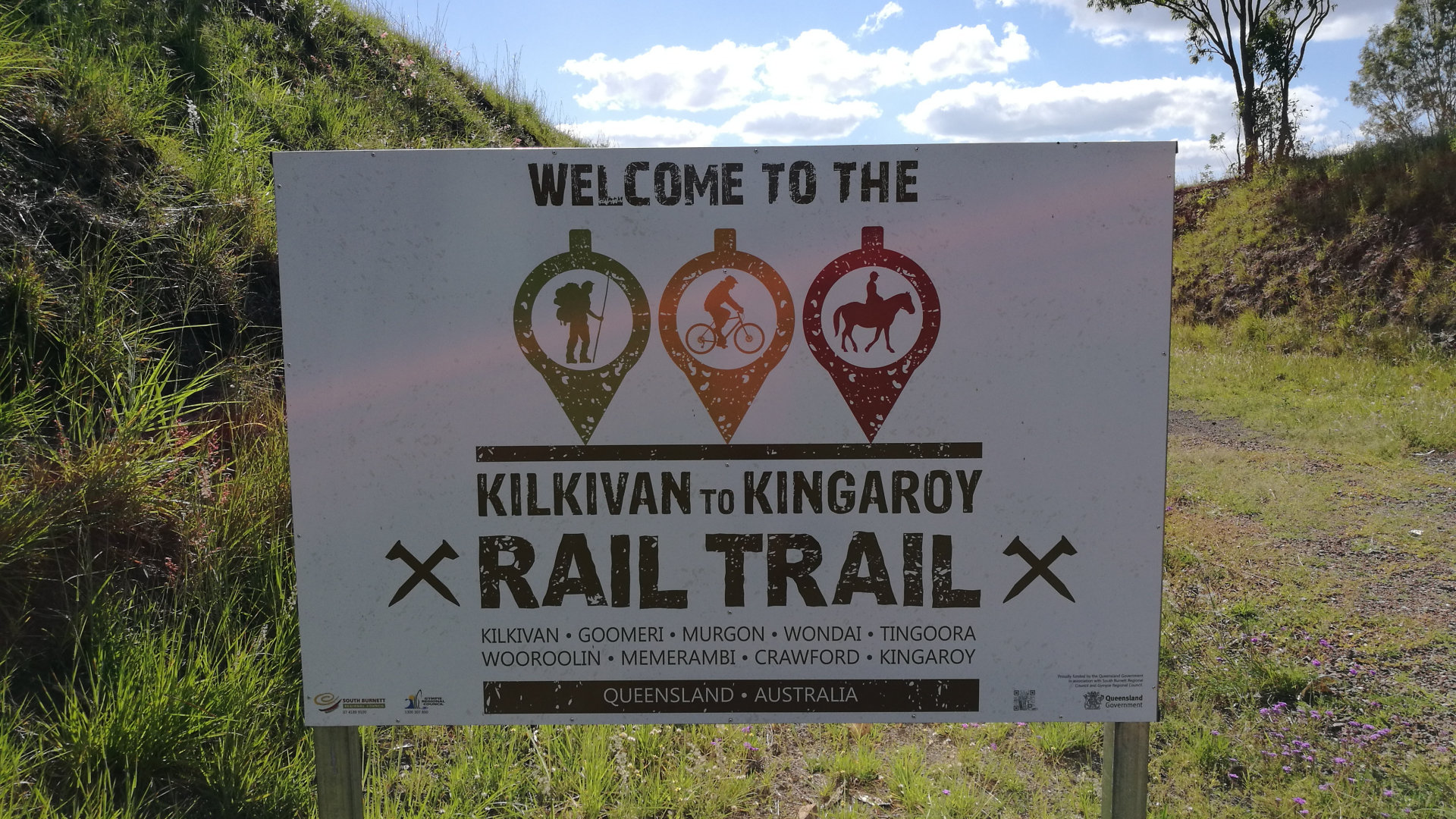 Sign at the start of the Kilkivan to Kingaroy Rail Trail. It reads Welcome to the Kilkivan to Kingaroy with the towns listed underneath. Symbols for hiking, bike riding, and horseriding