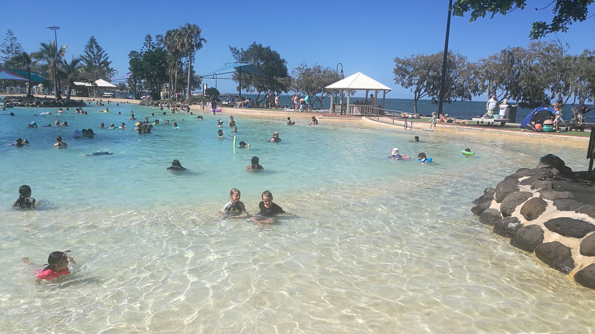 Settlement Cove Lagoon with plenty of people enjoying the cool water, also known as Redcliffe Lagoon, a free water park on Moreton Bay at Redcliffe. Very popular with families, shallow through to deep sections, BBQs and picnic tables