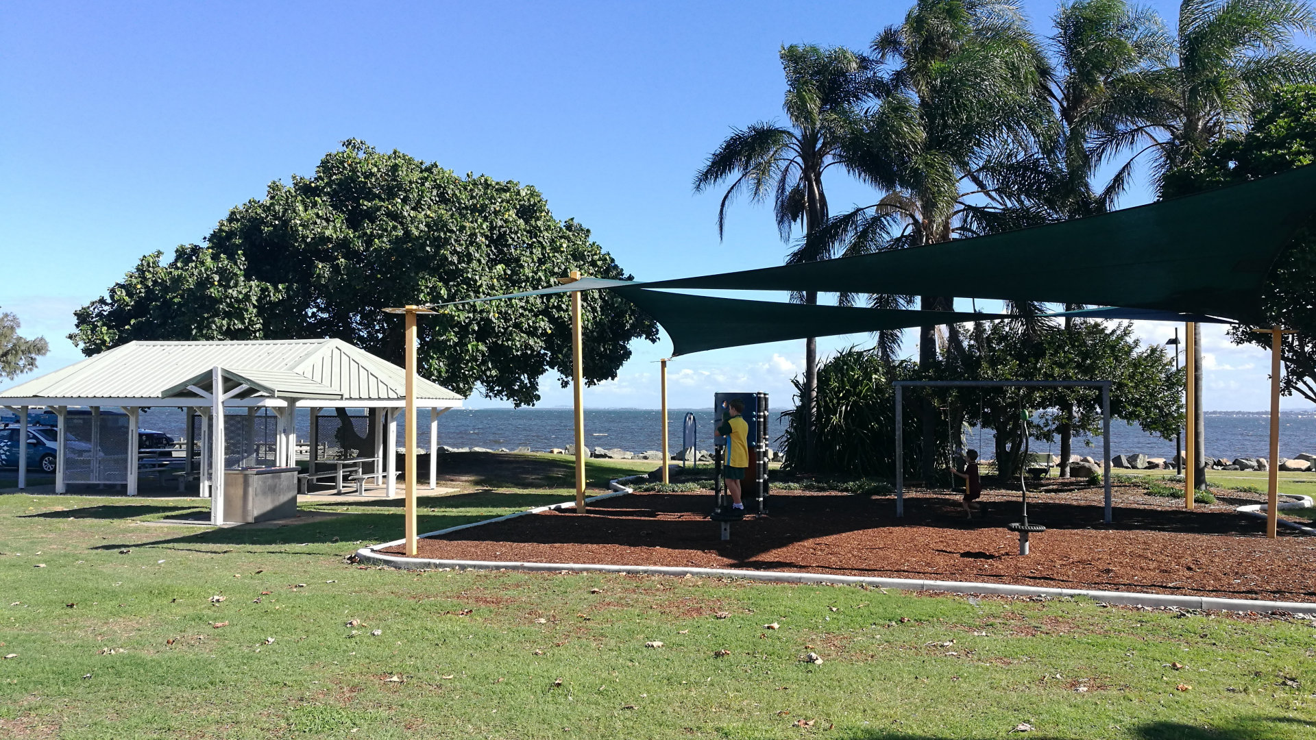 Playground and picnic tables at Bicentennial Park at Woody Point on the Redcliffe Peninsula. It has picnic tables, BBQs, children's playground, and a parkour park