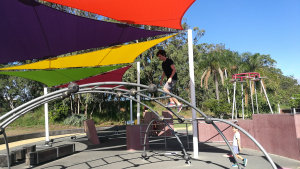 Person walking on bars at a parkour park, at the Bicentennial Park in Redcliffe
