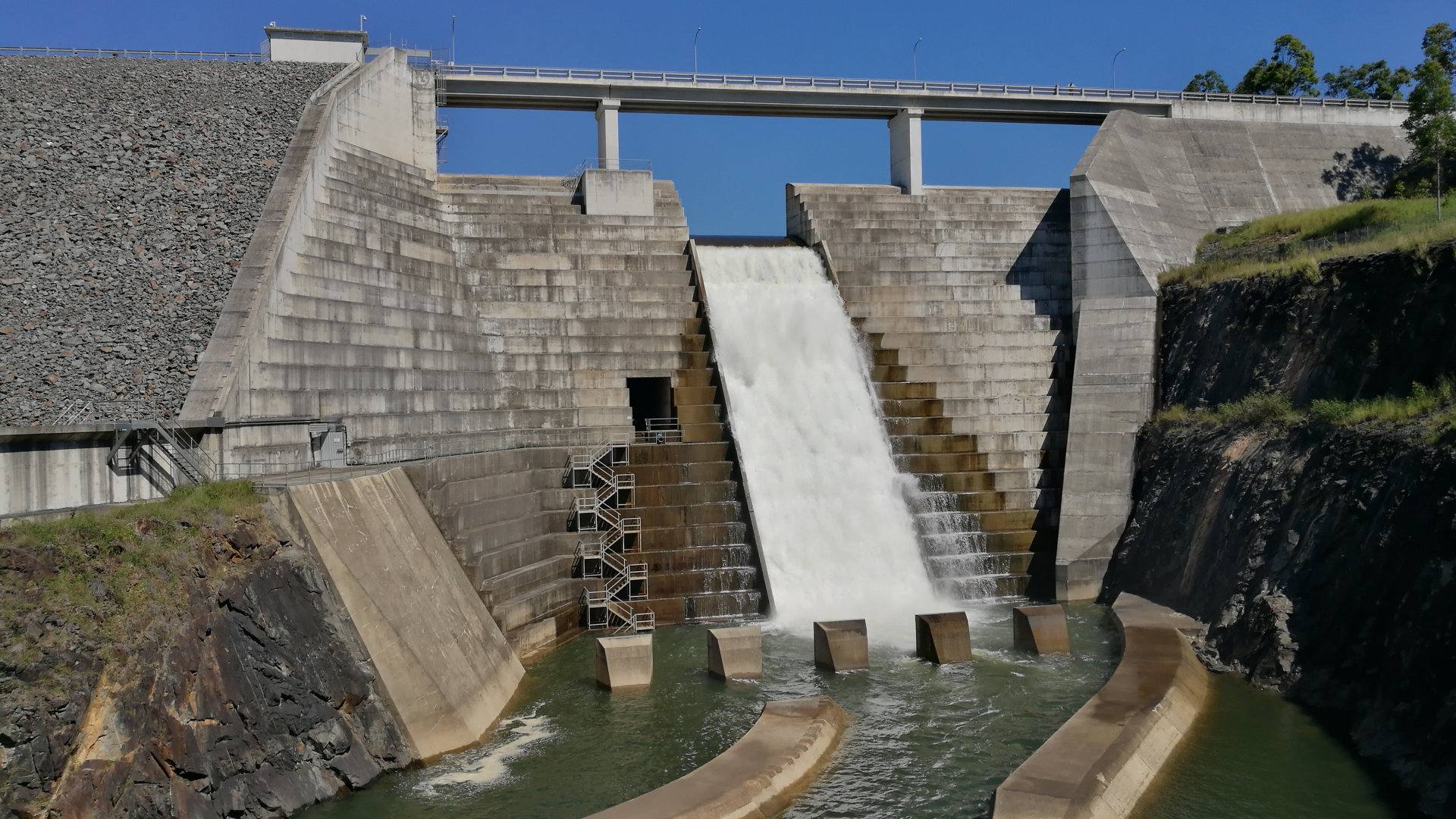 Hinze Dam spillway with water flowing over it. Hinze Dam is Gold Coast's main water supply. It has picnic areas with BBQs and tables, views of the dam, and mountain bike trails at the other end on the dam wall