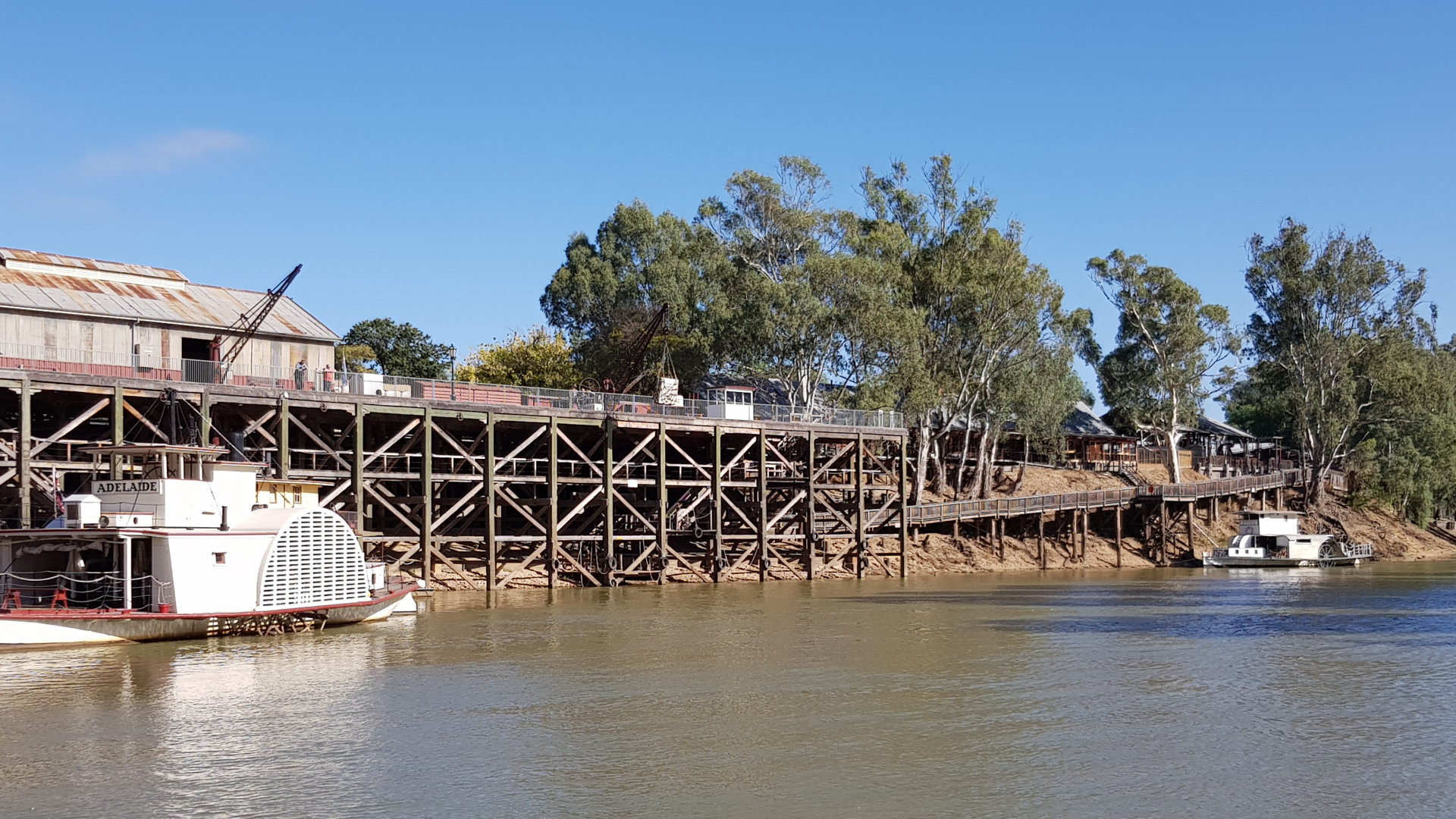Wharf at The Historical Port on the Murray River in Echuca with PS Adelaide in front. The wharf was built in 1865 to support sawmills in the area. The wharf is three stories high, and in its heyday over a quarter of a mile long. Visit the discovery centre, guided tours, and paddle steamer cruise