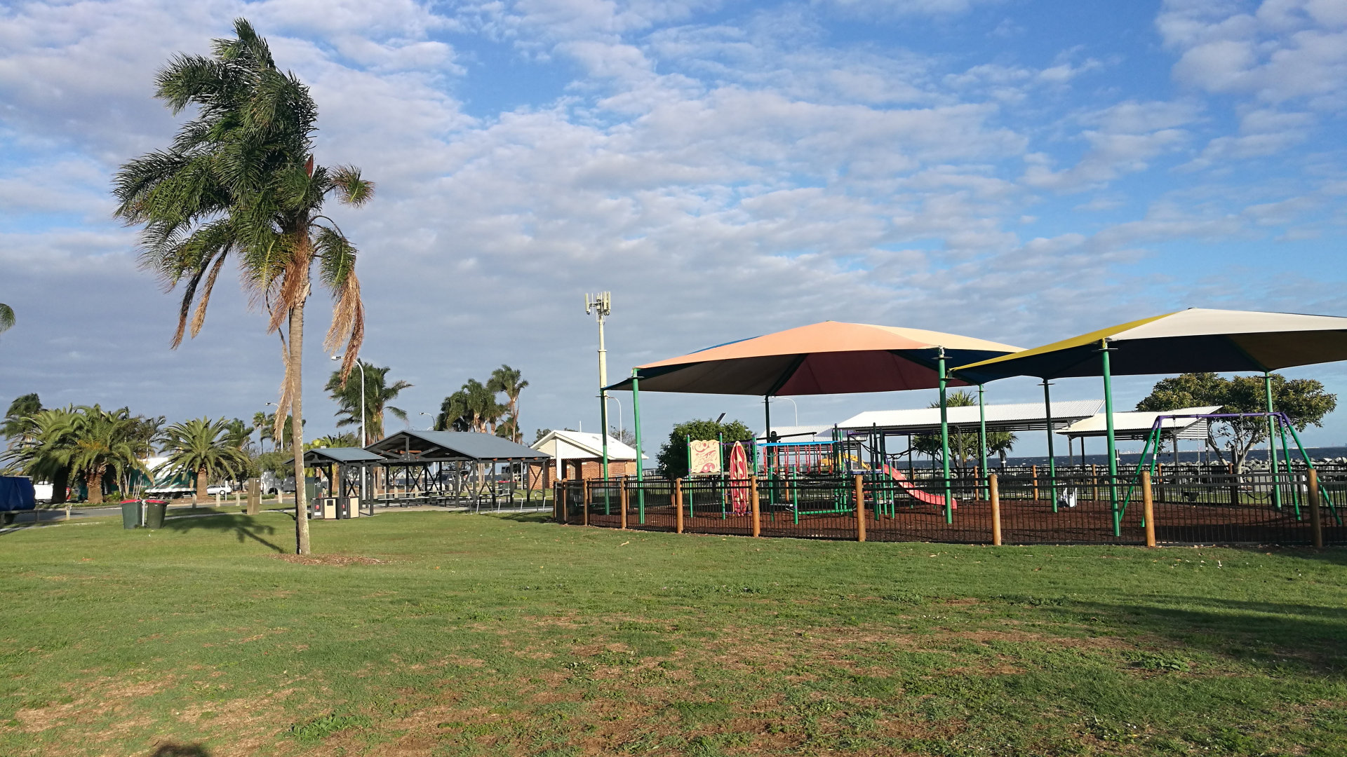 Playground and picnic tables at Pelican Park in Clontarf on the Redcliffe Peninsula. The park gets its name from the pelicans that visit the area, with views across the water of the bridge, Brisbane City, and Woody Point Jetty