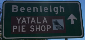 Brown sign for Yatala Pie Shop on a green sign for Beenleigh