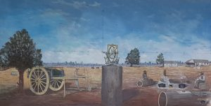 A mural at the Black Stump at Blackall depicting surveying apparatus on a stump by local artist Bob Wilson was made in 1993