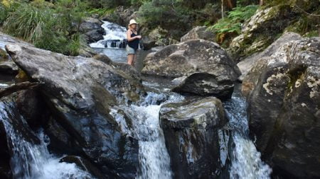 Woman standing in a waterhole with a waterfall in the background and another waterfall in the background, taken of Fiona Greenhill at Booloumba Creek in Conondale National Park, half way to the main Booloumba Creek Falls