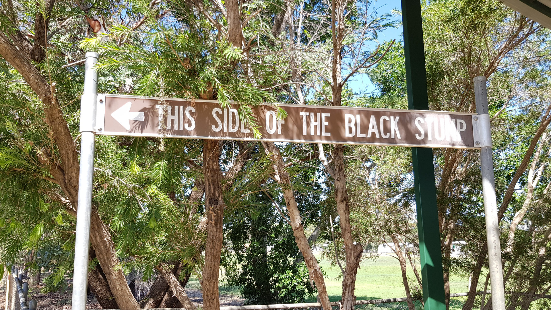"Brown sign of ""This Side of the Black Stump"" in Blackall. It is used to convey a perceived eastern border in Australia for where civilisation is contained. The Black Stump monument in Blackall has the brown tourist sign to define the location of the border."