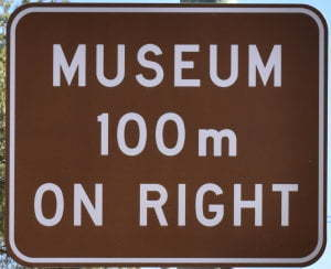 Brown sign for Museum, 100m on right