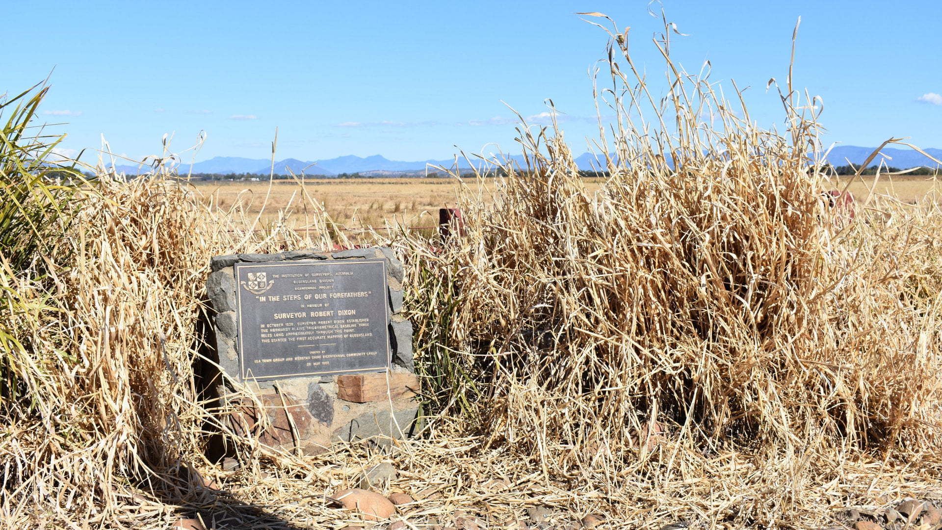 Historical Marker on the side of the road. The marker is in honour of surveyor Robert Dixon on the Normanby Plains Trigonometrical Baseline. The baseline was established in 1839 and started the accurate mapping of Queensland