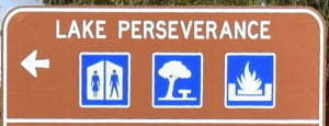 Brown sign for Lake Perseverance, with blue symbols for toilets, picnic area, and fireplace