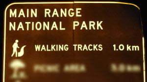 Brown sign for Main Range National Park Walking Tracks, 1km, symbol for walking tracks