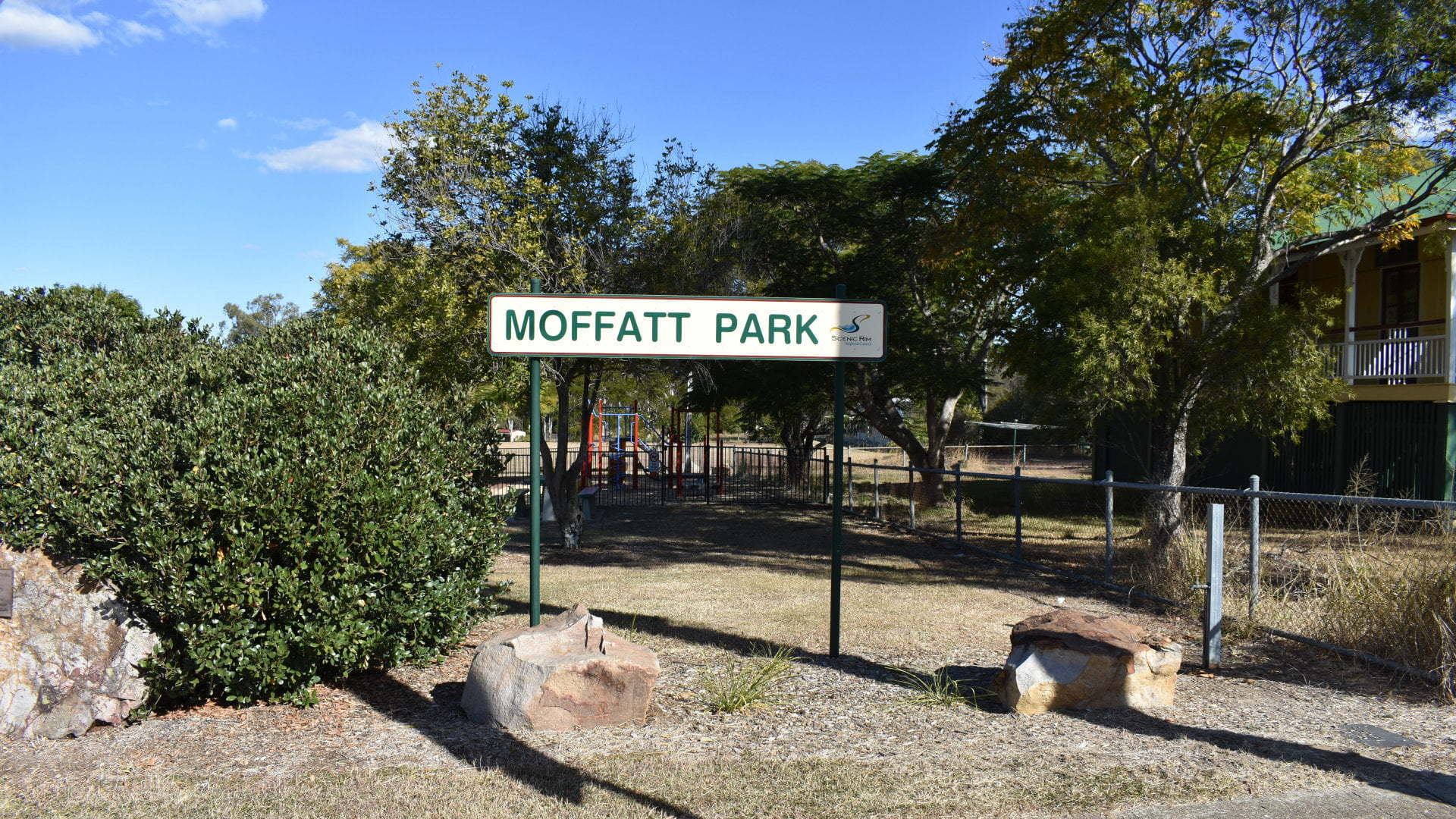Entrance and sign for Moffatt Park, a small playground park at Aratula with a fenced-in playgroundand a picnic table beside it