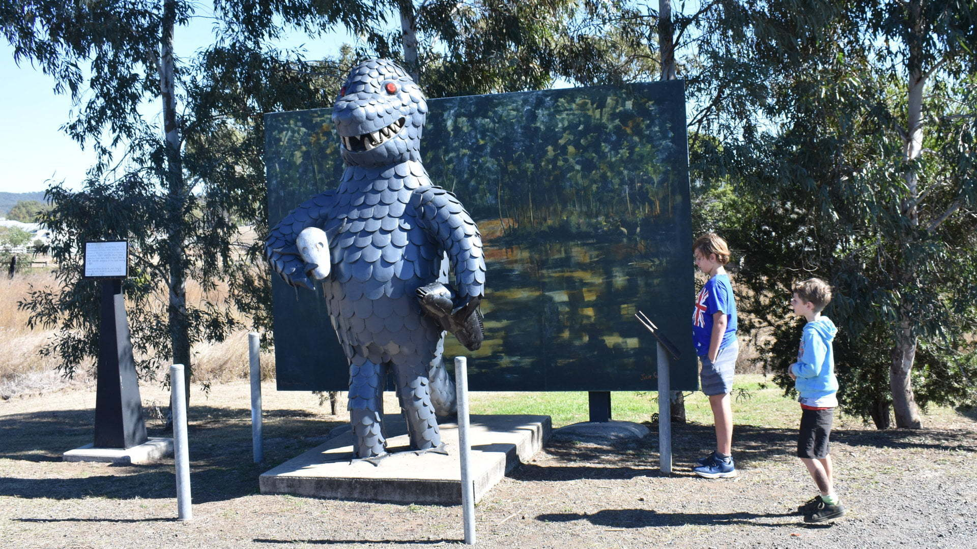 Sculpture of a bunyip in front of a mural, at the Bunyip Statue in Mulgildie