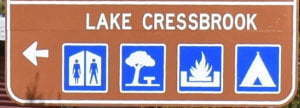Brown sign for Lake Cressbrook, blue symbols for toilets, picnic area, wood BBQs, and camping