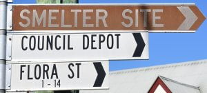 Brown sign for Smelter Site, also showing white street signs for Council Depot and Flora St