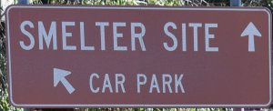 Brown sign for Smelter Site straight ahead and Car Park towards the left