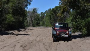 Wide dark sand track, Jeep Wrangler on the right hand side, on the access track to the Ocean Beach on Bribie Island