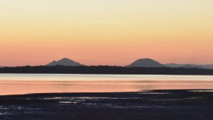 Sunset over water passage with mountains in the background, from Poverty Point on Bribie Island looking towards the Glasshouse Mountains