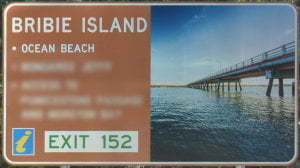 Brown sign for Bribie Island, Ocean Beach, Exit 152, with a picture of the bridge to Bribie Island