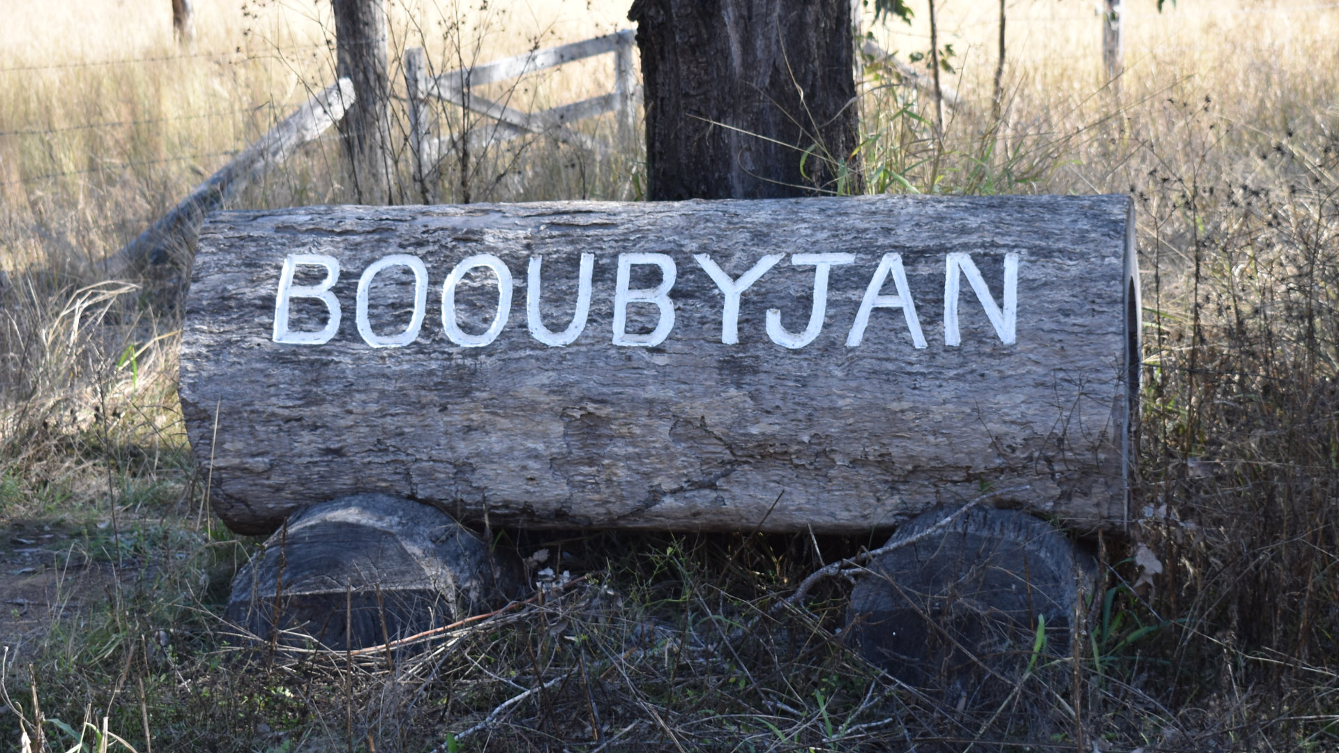 Log with BOOUBYJAN engraved and painted white onto it, at the entrance to the historic homestead on Booubyjan Station, originally 281 square miles and one of the earliest pastoral leases in Queensland