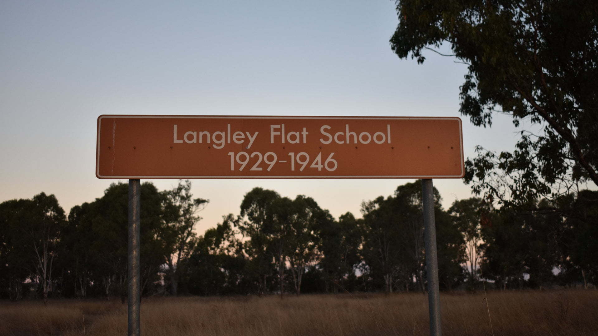Brown sign for Langley Flat School 1929-1946 in a paddock beside the Burnett Hwy, near the Monto-Mount Perry Rd
