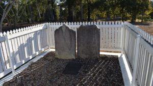 Grave site with two headstones surrounded by a white picket fence, at the Pioneer Graves location in Maryborough