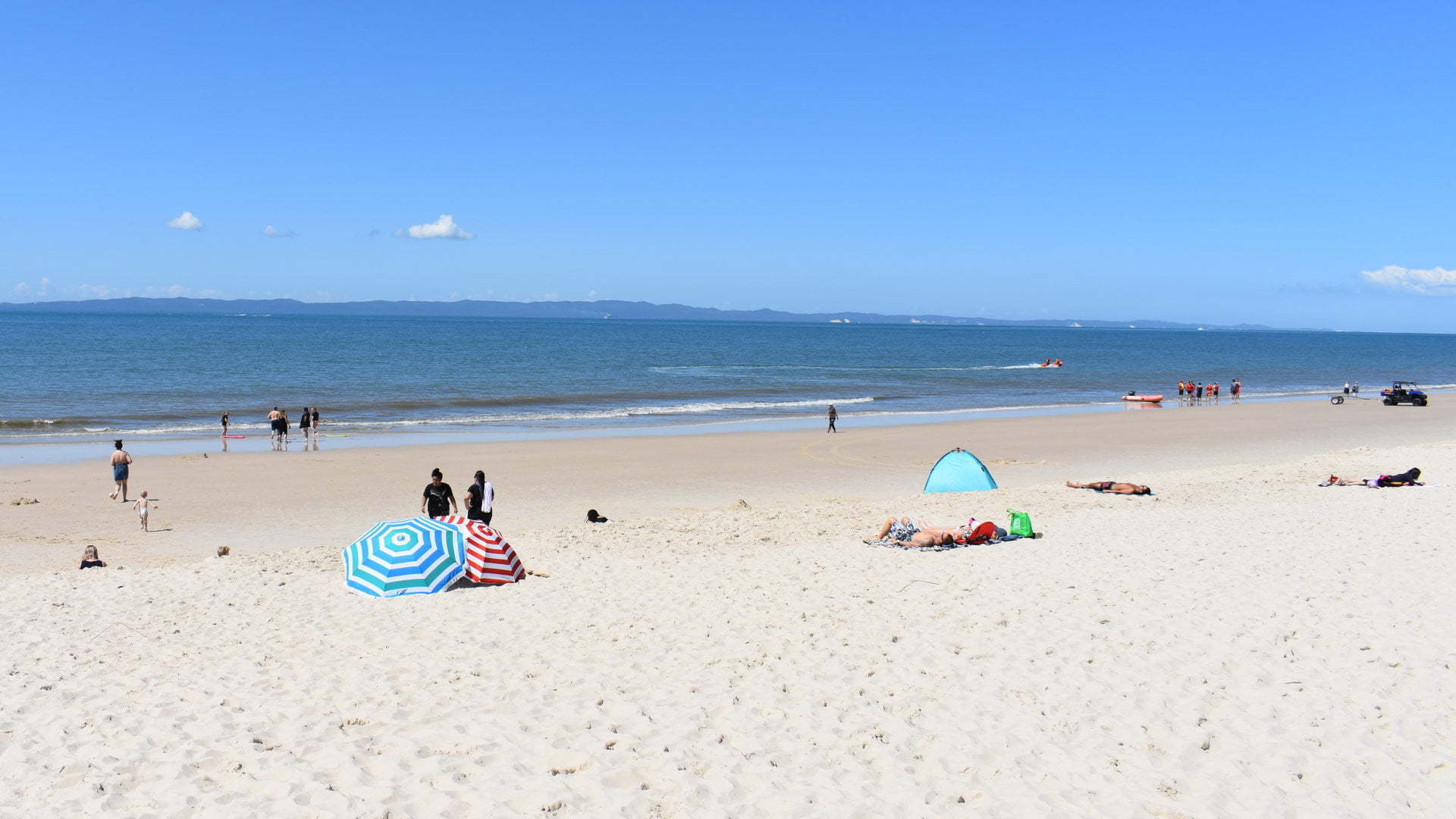 Surf Beach, people on the beach, beach umbrella, from the surf beach on Bribie Island and Moreton Island across the water in the distance, lifesavers with a boat to the right