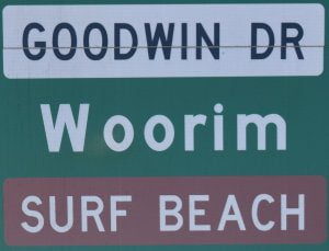 Brown sign for Surf Beach, on a green sign for Woorim, with white sign for Goodwin Dr