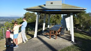 Picnic tables under a shelter and boys looking at the view from the lookout, at Dulong Lookout