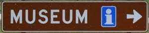 Brown sign for Museum, with a blue and white information centre symbol