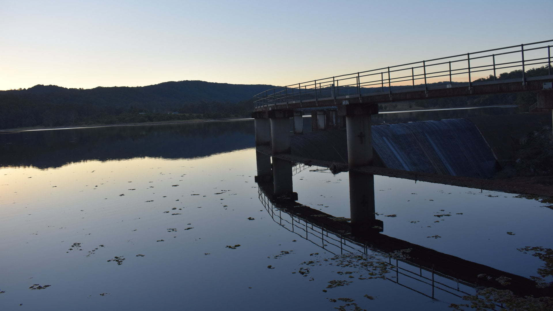 Late afternoon dam surface with mountain hills in the background and curved dam wall to the right, Wappa Dam near Yandina