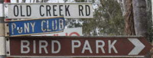 Brown sign for Bird Park, white sign for Old Creek Rd, Blue sign for Pony Club