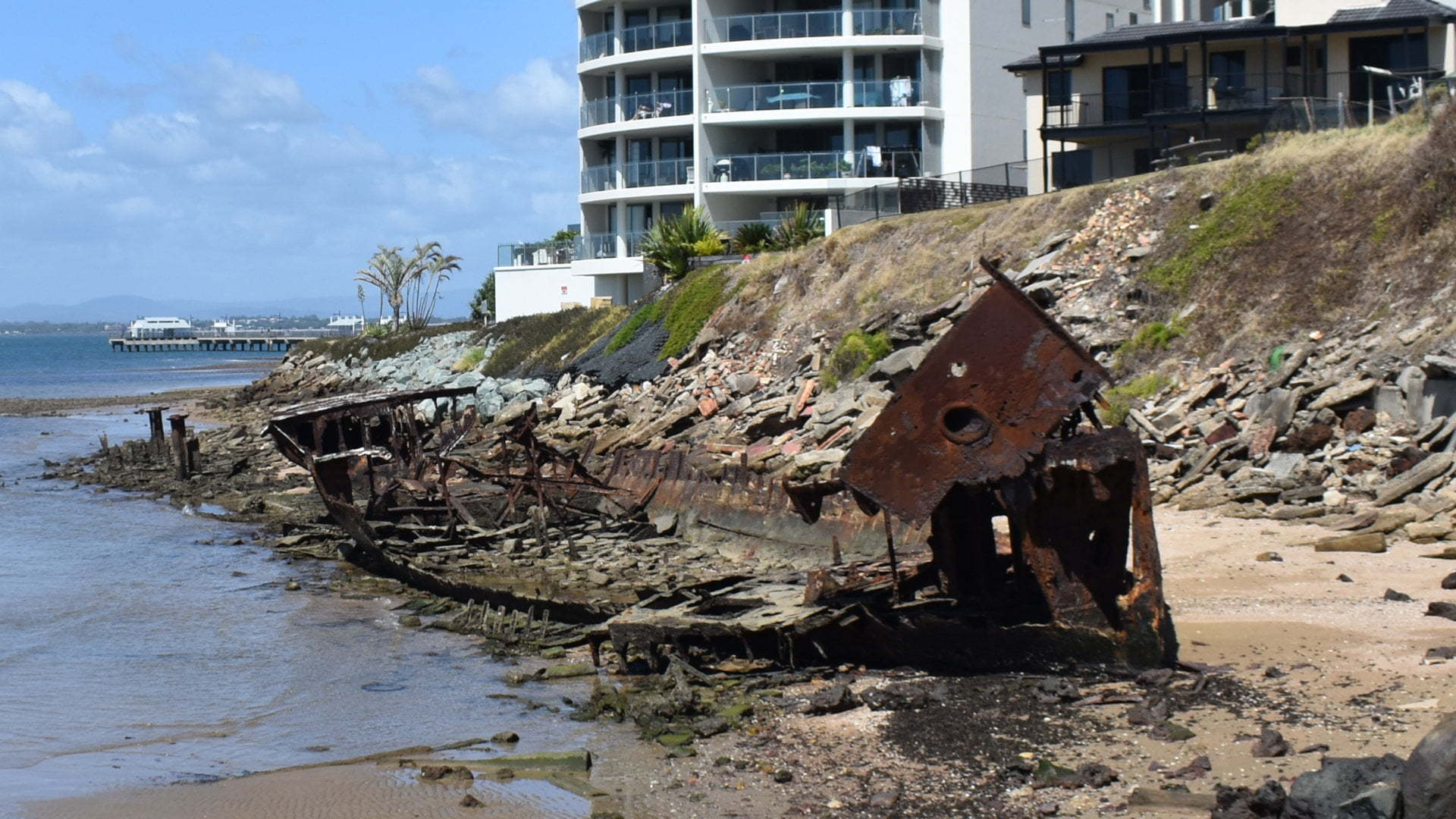 Rusted wreck on a beach near cliffs, the Gayundah Wreck at Woody Point in Redcliffe
