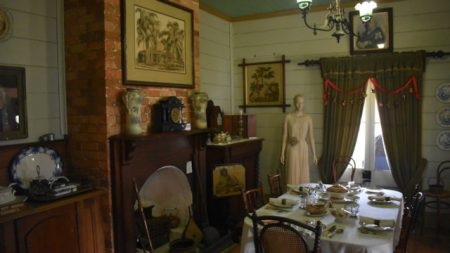 Dining room in the Buderim Pioneer Cottage, dining table with place settings, fire place with exposed brick chimney, mantle place clock
