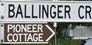 Brown sign for Pioneer Cottage, white sign for Ballinger Cr