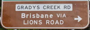 Brown sign for Brisbane via Lions Road, white sign for Gladys Creek Rd