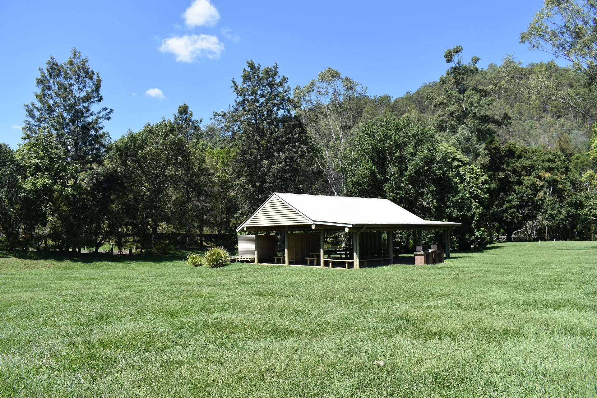 Open grass area and picnic shelter with picnic tables and BBQs, at Red Cedar Park in the southern section of D'Aguilar National Park