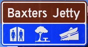 Brown sign for Baxters Jetty, blue sign with symbols for toilets, shaded picnic table, boat ramp