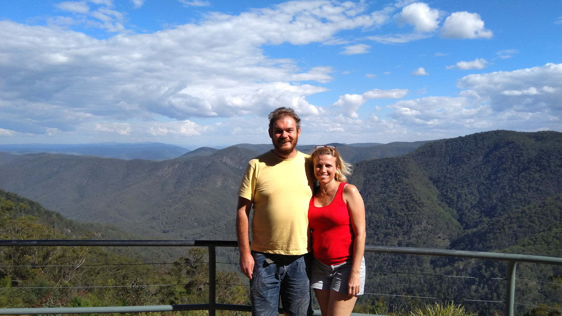Two people standing at the lookout of mountains and valleys, taken at Raspberry Lookout in the Gibraltar Ranges National Park