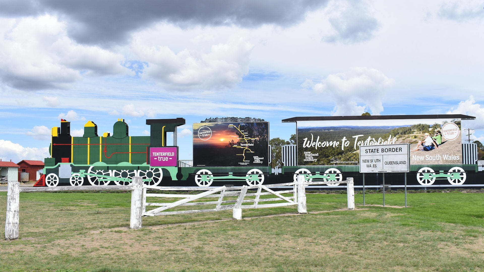 Billboard in the shape of a train, white wooden post fence, sign showing the border of Queensland and New South Wales