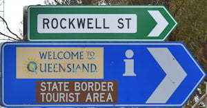 Brown sign for State Border Tourist Area, unaccredited information sign with Welcome to Queensland, green sign for Rockwell St