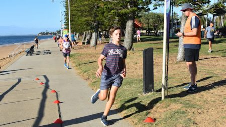 A person running along a path, at the finish line of Redcliffe Parkrun at Suttons Beach