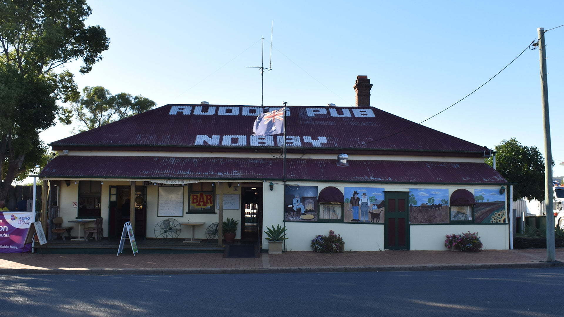 The front of a country pub with Rudd's Pub Nobby written on the roof, the pub of Dad and Dave's fame from Rudd Steele