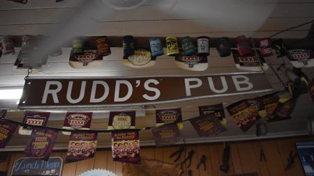 Brown sign for Rudd's Pub hanging from the ceiling above the bar