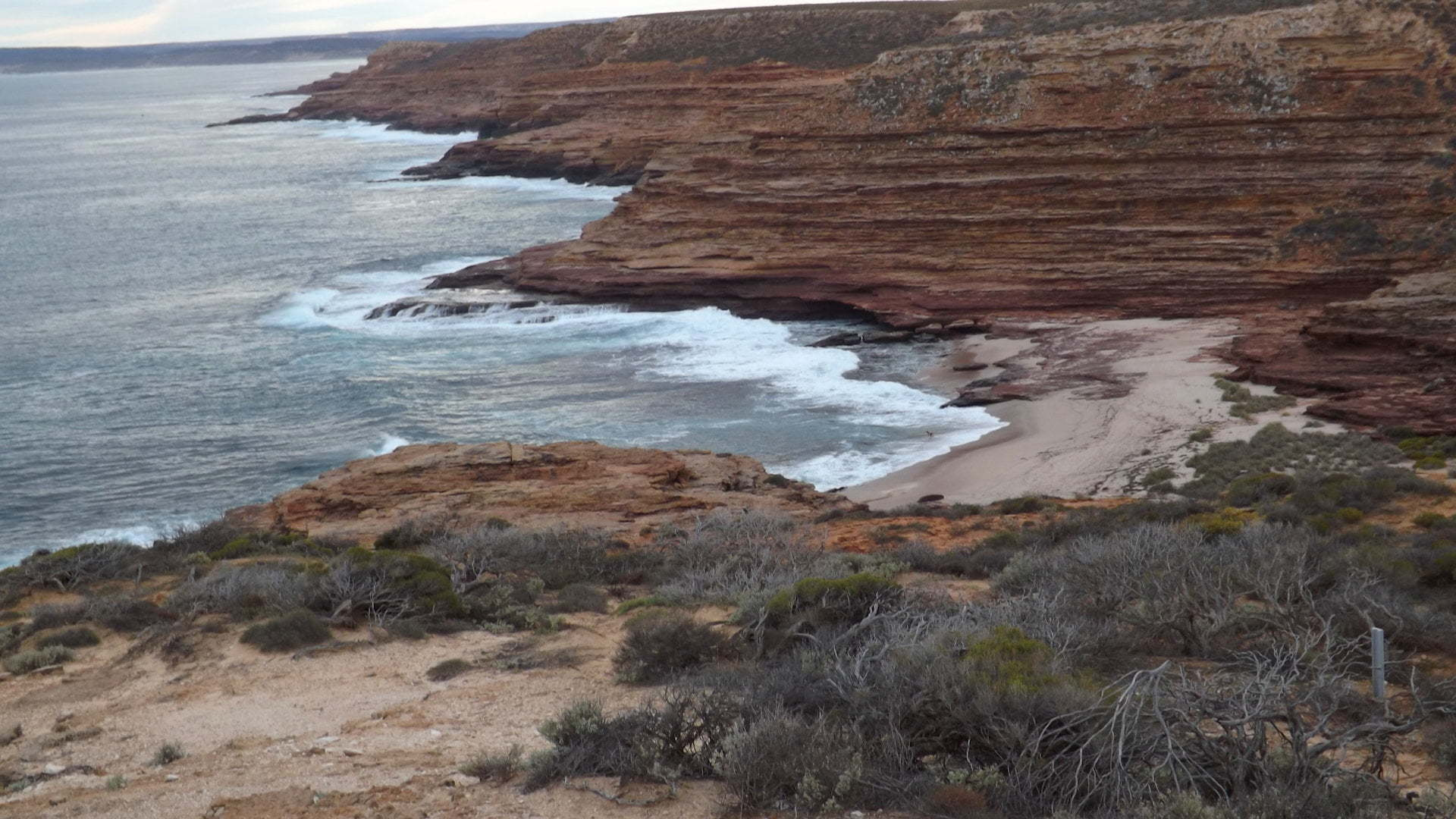 Red sandstone cliffs and a beach in a gorge, taken at Eagle Gorge in Kalbarri National Park
