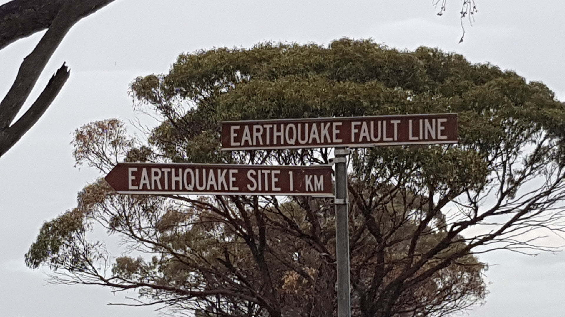 Brown sign of the Earthquake Fault Line taken at the site of where the fault line exists, also showing a brown sign to an Earthquake Site 1km away