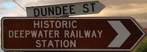 Brown sign for Historic Deepwater Railway Station, white sign for Dundee St
